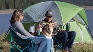 Couple sat outside tent with dog