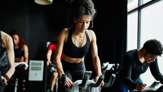 Are exercise bikes good for weight loss? Image of woman riding exercise bike in spin class gym