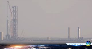 """The Super Heavy vehicle known as Booster 4 (left) sits on the orbital launch mount at SpaceX's Starbase site in South Texas on Sept. 8, 2021. This image is a screenshot of video footage taken by Spadre.com's """"Starship Cam."""""""