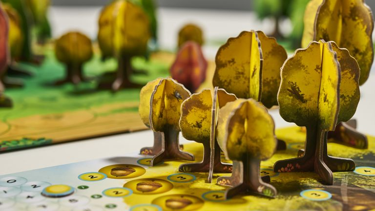 Best board games 2021, image shows Photosynthesis board game being played, with the player board showing several yellow trees, with the main board in the background