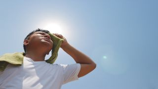 A man wiping sweat from his face under the hot sun.