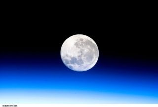 A full moon is visible in this view above Earth's horizon and airglow, photographed by Expedition 10 Commander Leroy Chiao on the International Space Station.