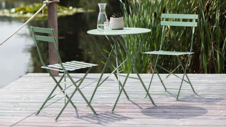 A green metal bistro set on decking overlooking a lake