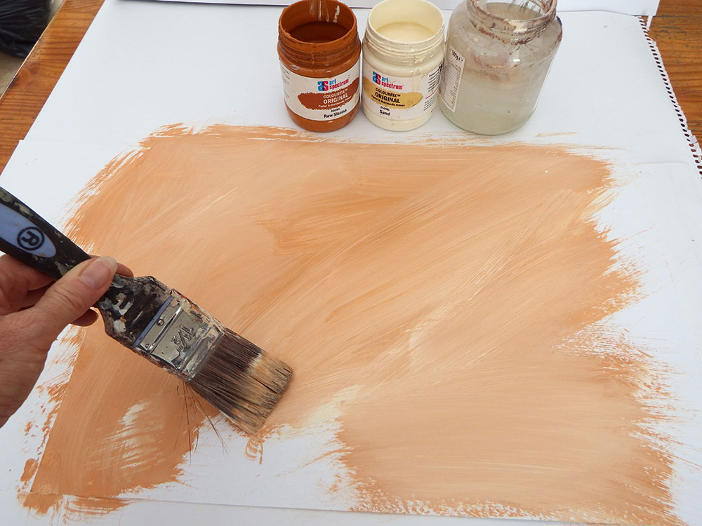 Photo of artist applying a tan-coloured primer