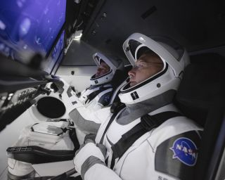 NASA astronauts Doug Hurley (foreground) and Bob Behnken (background) train in a simulator for SpaceX's Crew Dragon, getting used to the touchscreen controls