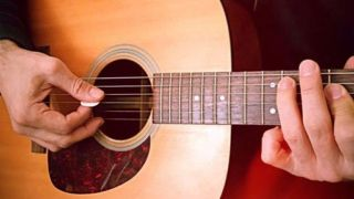 Close-up of hands on acoustic guitar