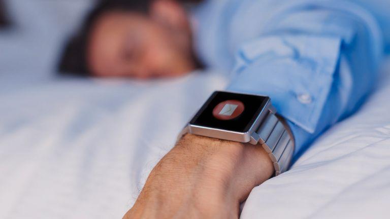 Man sleeps on bed wearing a fitness tracker