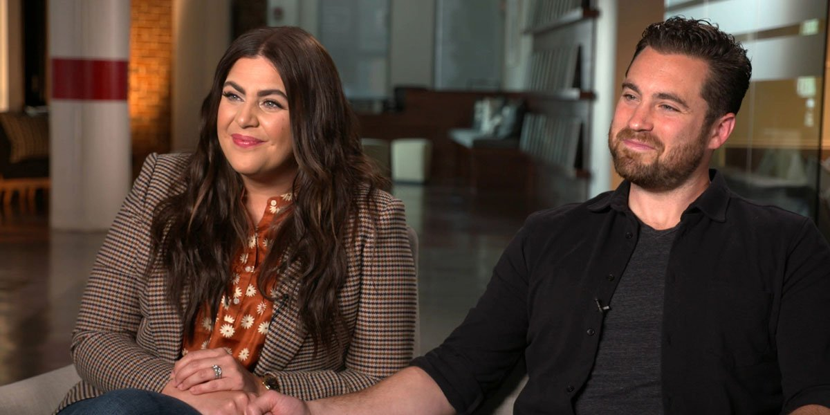 Hillary Scott from Lady A and her husband Chris Tyrrell sitting for an interview while holding hands.