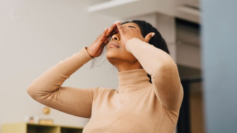 Woman holding her head, feeling burnt out during work