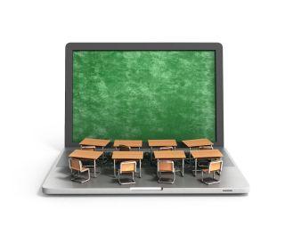 Student desks atop laptop computer with green screen like blackboard.