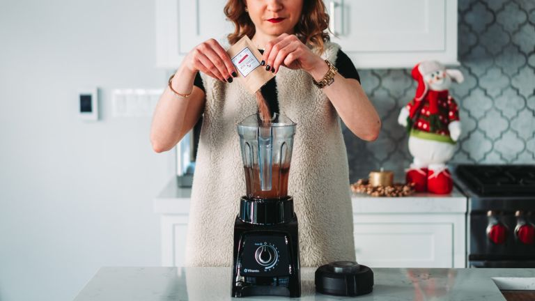 A woman prepares a healthy smoothie with one of the best blenders