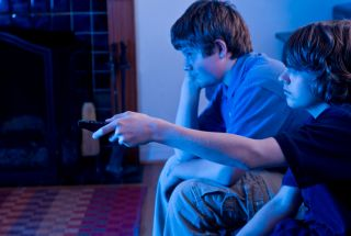 Two boys sit in a dark room watching television
