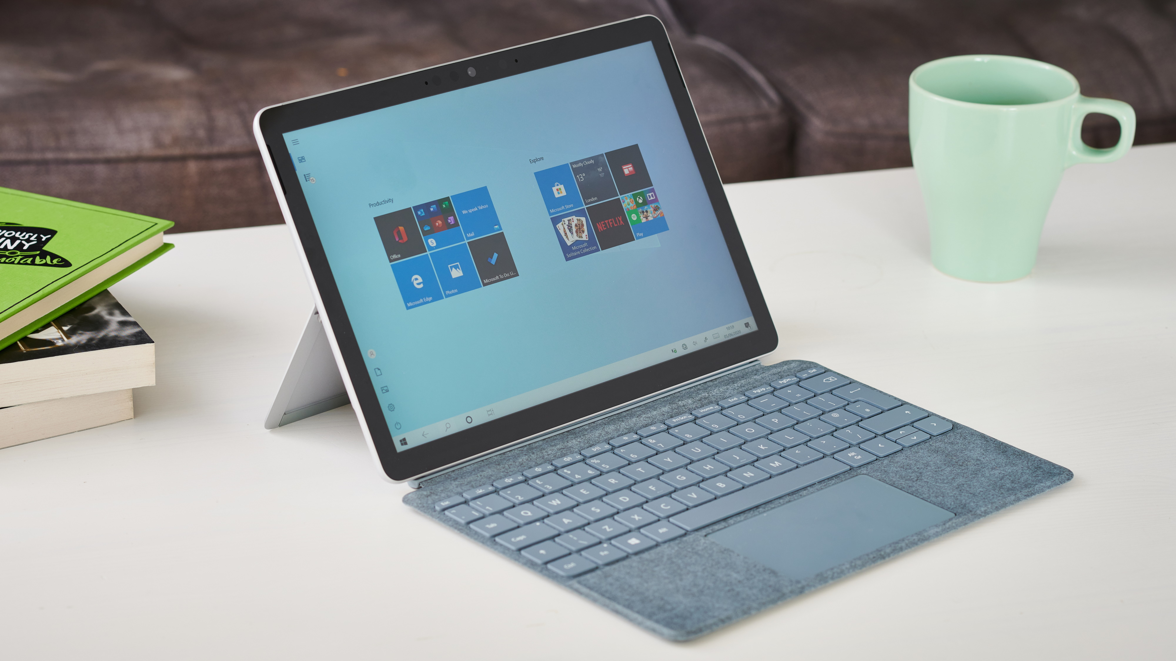 Microsoft Surface Go 2 on a white coffee table next to a stack of books and a mint coffee cup