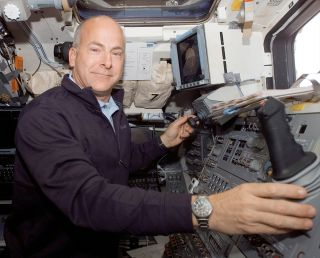 Astronaut Alan Poindexter works on the aft flight deck of space shuttle Atlantis during his first spaceflight in 2008.