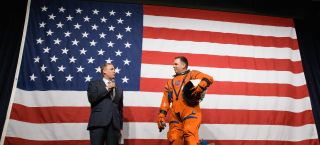 NASA Administrator Jim Bridenstine (left) talks to Dustin Gohmert, the Survival Systems Project Leader of the Orion Crew at Johnson Space Center NASA's Survive Suit of the Orion Crew, on the suit, Tuesday, October 15, 2019 at NASA Headquarters in Washington.