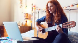 Girl plays acoustic guitar in front of a laptop