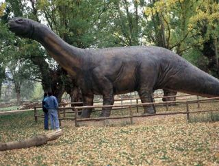 Visitors look at a model of a sauropod dinosaur.