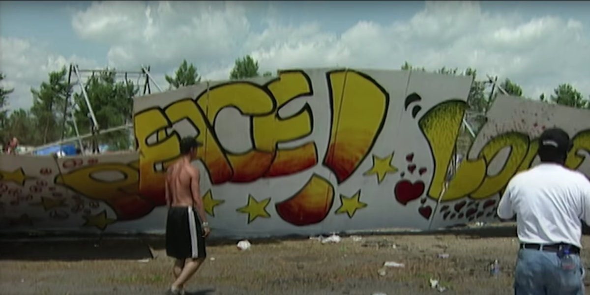 Woodstock attendees tear down a wall in the Woodstock '99: Peace, Love, and Rage trailer