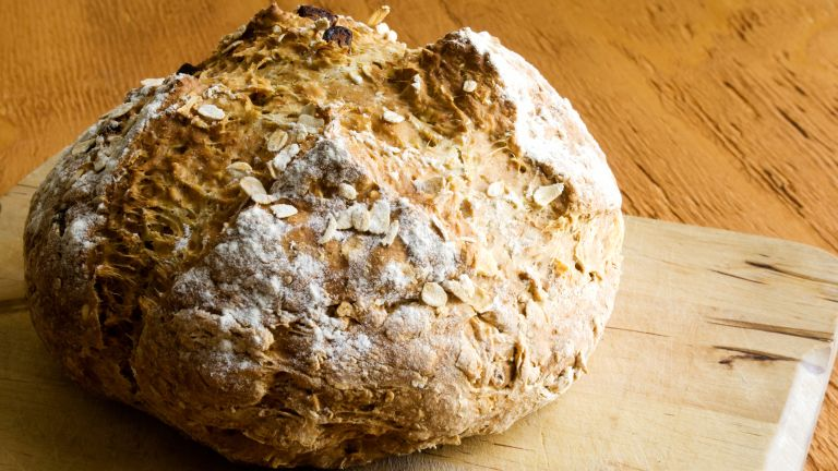how to make soda bread: a loaf of soda bread with raisins on a chopping board