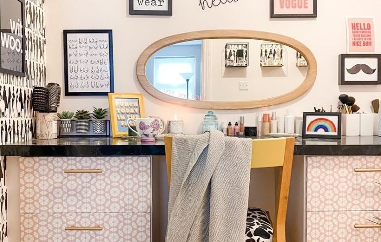 dressing room with patterned drawers, a mirror and a gallery wall above a dressing table