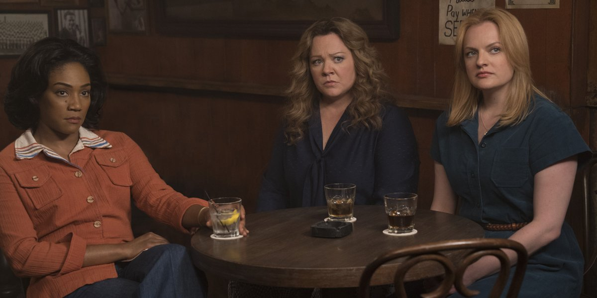 Melissa McCarthy, Tiffany Haddish, and Elisabeth Moss sit at a table drinking in The Kitchen