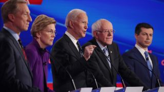 Tom Steyer (L), Sen. Elizabeth Warren (D-MA), Sen. Bernie Sanders (I-VT) and former South Bend, Indiana Mayor Pete Buttigieg (R) listen as former Vice President Joe Biden (C) speaks during the Democratic presidential primary debate at Drake University on Jan. 14, 2020 in Des Moines, Iowa.