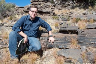 University of Cincinnati geologist Andrew Czaja points to a section of black chert in Northern Cape province, South Africa, where microscopic fossils that may be the oldest known sulfur oxidizers were found. The bacteria lived 2.52 billion years ago.