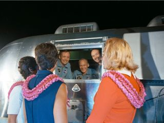 After returning home from the moon, the Apollo 11 crew is greeted by their wives while they are in the Mobile Quarantine Facility (MQF).