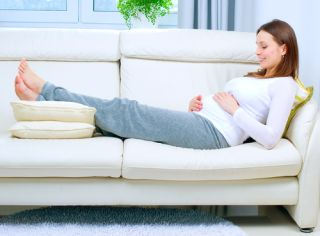 A pregnant woman rests on a couch with her feet elevated.