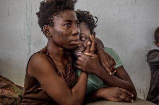 Two woman cling onto each other bravely. One has a tear rolling down her cheek, but looks ahead resolutely, while the other partially hides her face.
