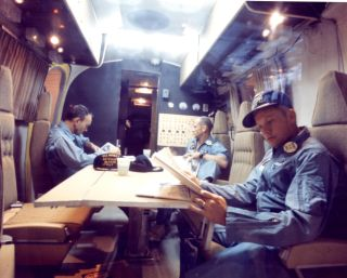 Michael Collins, Buzz Aldrin and Neil Armstrong seen inside the Mobile Quarantine Facility during the 2.5-day trip back to port on the USS Hornet, which picked them up when they splashed down.