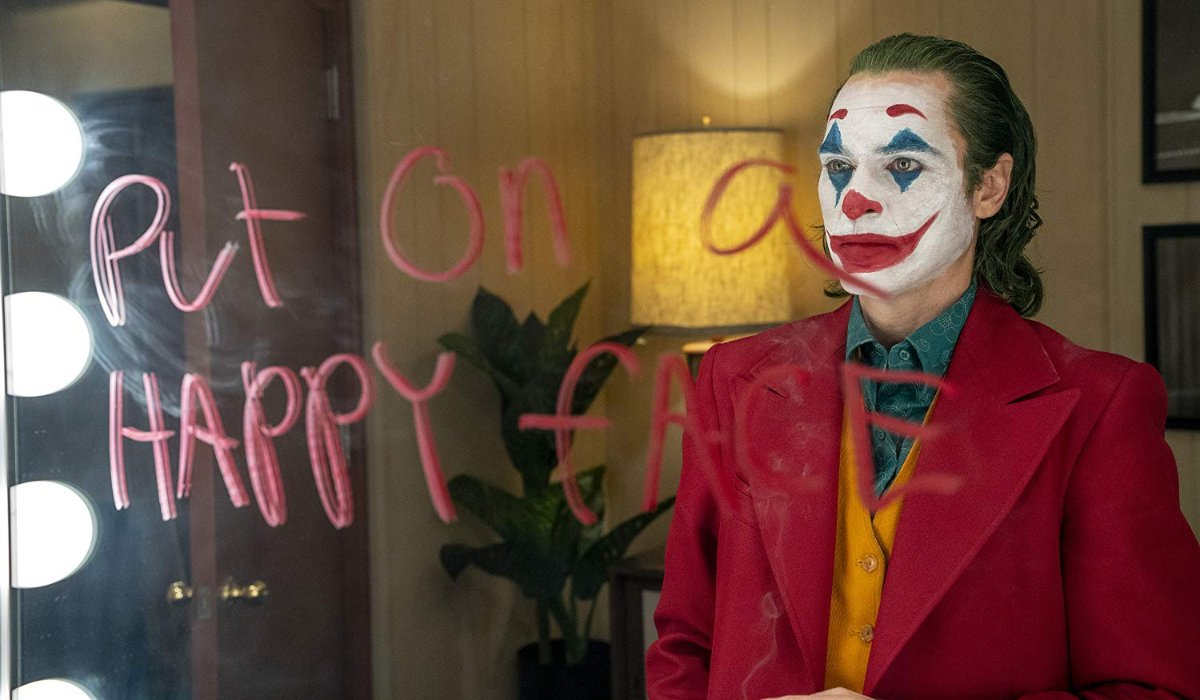 Joker staring at the message on his mirror, angered