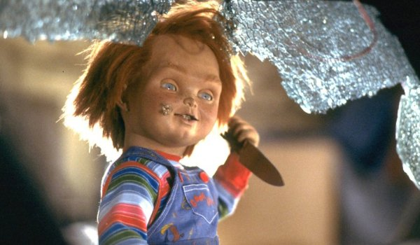 Child's Play Chucky holds a knife framed by a shattered window