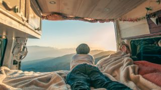 A camper looking out of a camper van window