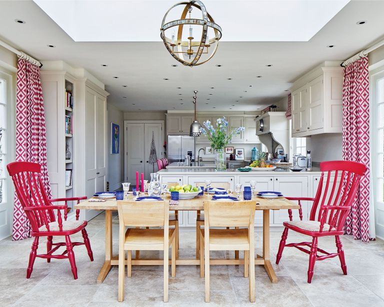 Red kitchen ideas in a pale gray scheme with red patterned drapes and chairs.