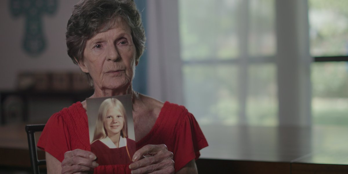 Joyce Lemons holding up a photo of a girl in The Confession Killer
