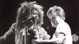 Tina Turner and Bryan Adams on stage performing It's Only Love