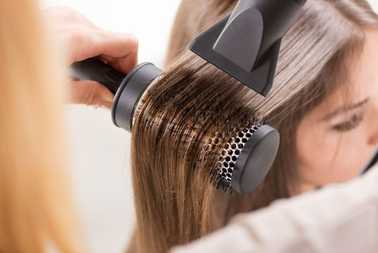 Best hair dryer: blow drying brunette hair with brush