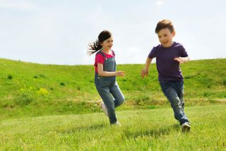 Children play tag in a green field