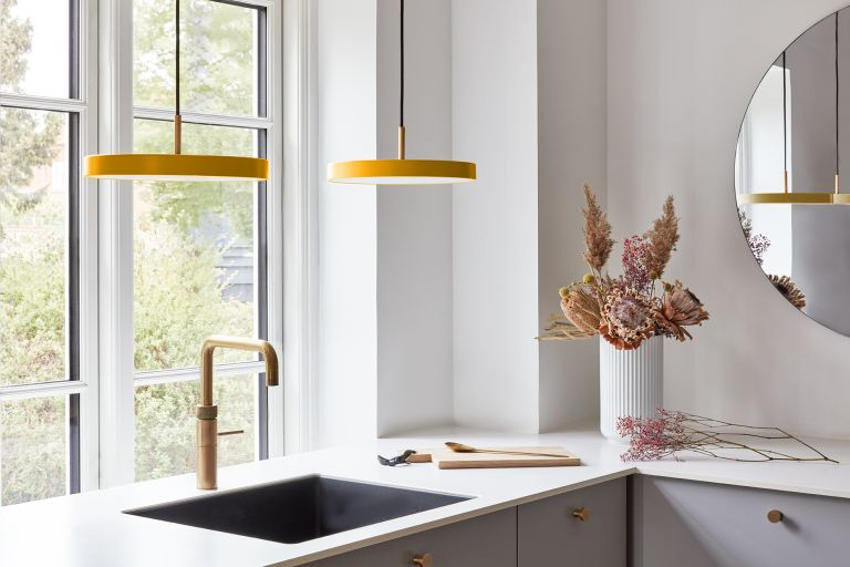 modern yellow pendant lights over a basin with brass tap, white countertop