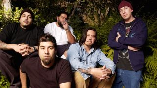 Deftones sitting surrounded by plants
