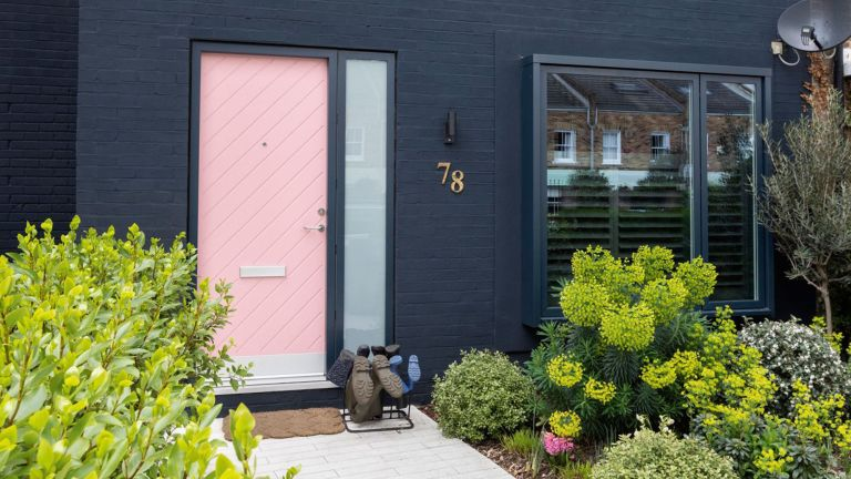 Dark house with pink door and lush front garden