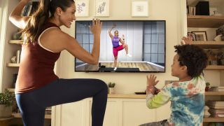 Peloton Digital review: A woman and child work out using the Peloton app on their TV