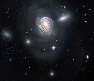 Cosmic Photo Reveals Majestic Spiral Galaxy In Packed Cluster