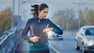 Woman running by a road, checking her running watch