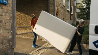 How to dispose of a mattress: Two people carry a mattress into the back of a white van