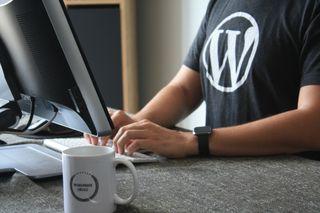 man in WordPress shirt working at desk on computer