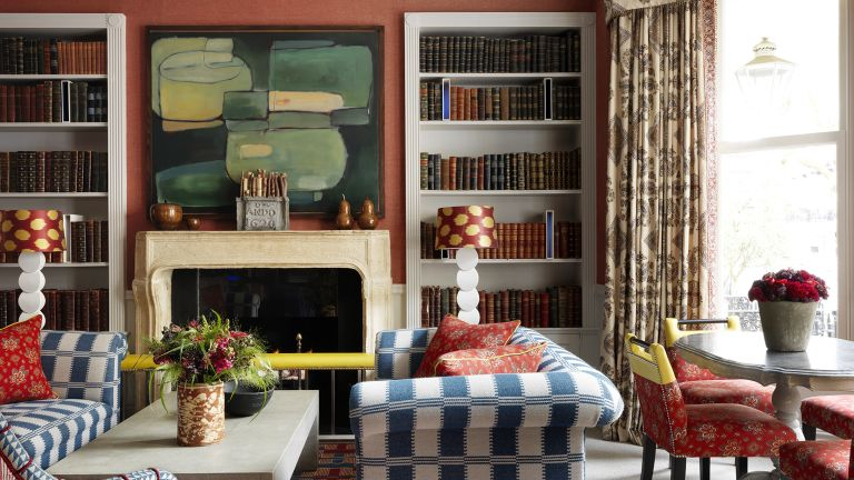 Fall color schemes in a living room with burnt orange walls, blue and white striped sofas and sand-colored mantel