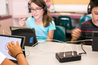 Kids using headphones, tablets and ThinkWrite charging hub in classroom