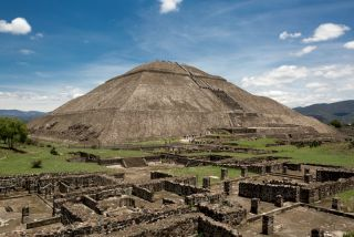 The Pyramid of the Sun in the ancient city of Teotihuacan with ruin walls in the foreground.